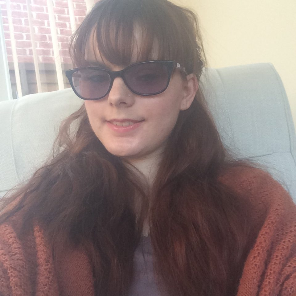 Naomi sat in a chair wearing sun glasses